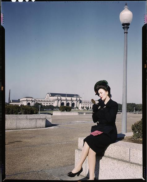 Flickr_-_The_Library_of_Congress_-_Woman_putting_on_her_lipstick_in_a_park_with_Union_Station_behind_her,_Washington,_D.C._(LOC)